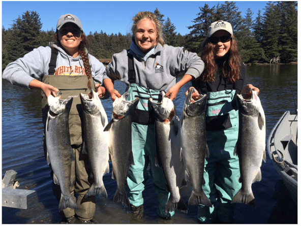 three girls holding sockeye salmon