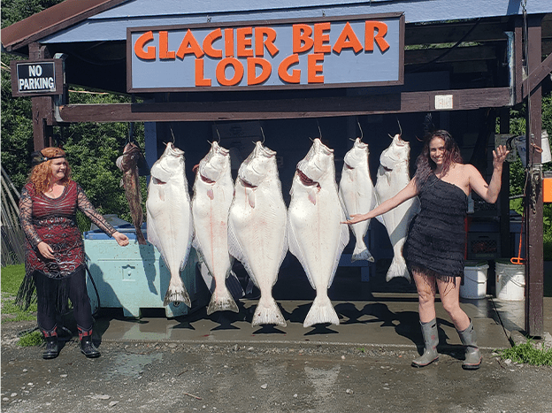 women posing with halibut